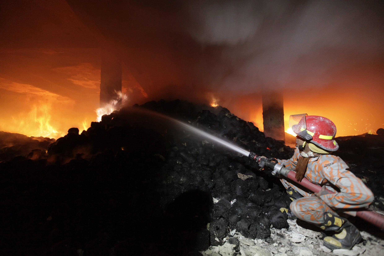 Bombeiro combate chamas na fábrica Tazreen Fashion, em Bangladesh, no sábado à noite.