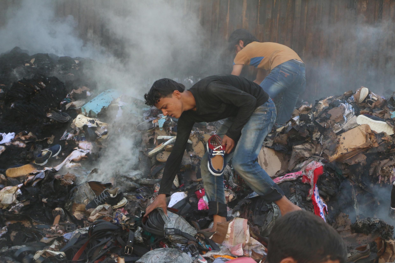Sírios tentam recuperar produtos de caminhão de ajuda humanitária atingido por bombardeio em Aleppo.