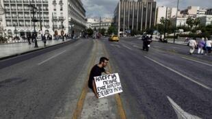 Un étudiant grec manifestant face au Parlement d'Athènes lors de l'annonce d'un nouveau plan d'austérité par le ministre des Finances du pays.