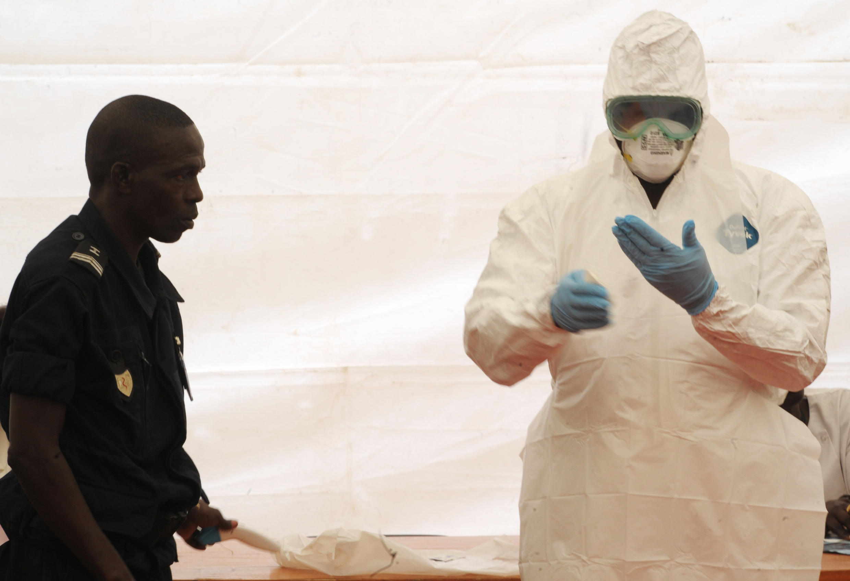 A l'aéroport de Dakar, un personnel sanitaire montre comment s'équiper pour se protéger d'Ebola, le 8 avril 2014.