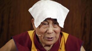 Le Dalaï Lama, 81 ans, a tenu une partie de sa conférence de presse avec une serviette humide sur sa tête à cause de la chaleur. Paris, le 13 septembre 2016.
