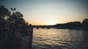 Parisienses se reúnem para ver o pôr do sol na margem direita do rio Sena.