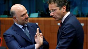 O comissário europeu de assuntos econômicos, Pierre Moscovici, conversa com o presidente do Eurogrupo, Jeroen Dijsselbloem.