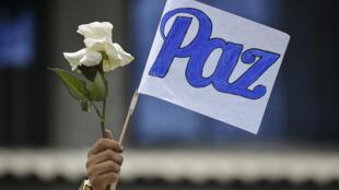 """Un hombre sostiene una flor y una bandera con la palabra """"Paz"""" durante el funeral dos de los seis hombres asesinados por presuntos miembros de un grupo armado el 21 de agosto en la zona rural de El Tambo, el 25 de agosto de 2020, en Popayan, Colombia"""