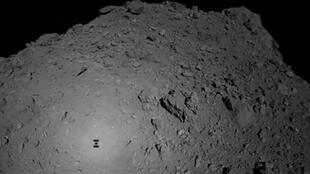 Handout photograph released Oct. 3 shows the shadow of Japanese spacecraft Hayabusa2 over the asteroid Ryugu