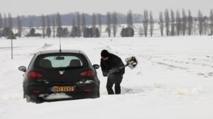 Por causa da neve a circulação ficou dificil no norte da França. Homem tenta desatolar seu carro em Cambrai, no norte da França.