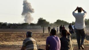 Des Kurdes regardent depuis le frontière turque les attaques du groupe Etat islamique sur la ville de Kobane, le 7 octobre 2014.