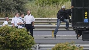 French police with a migrant who had climbed into a lorry entering the Channel Tunnel in Calais
