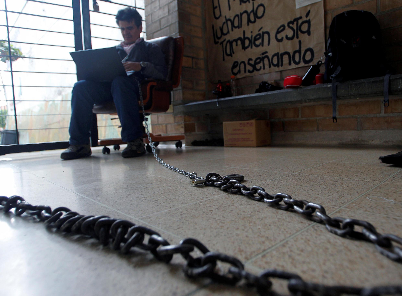 El profesor Carlos Fredy, encadenado a la puerta de la escuela, protesta por mejoras en el sistema escolar en Medellín, Colombia, este 8 de junio de 2017.