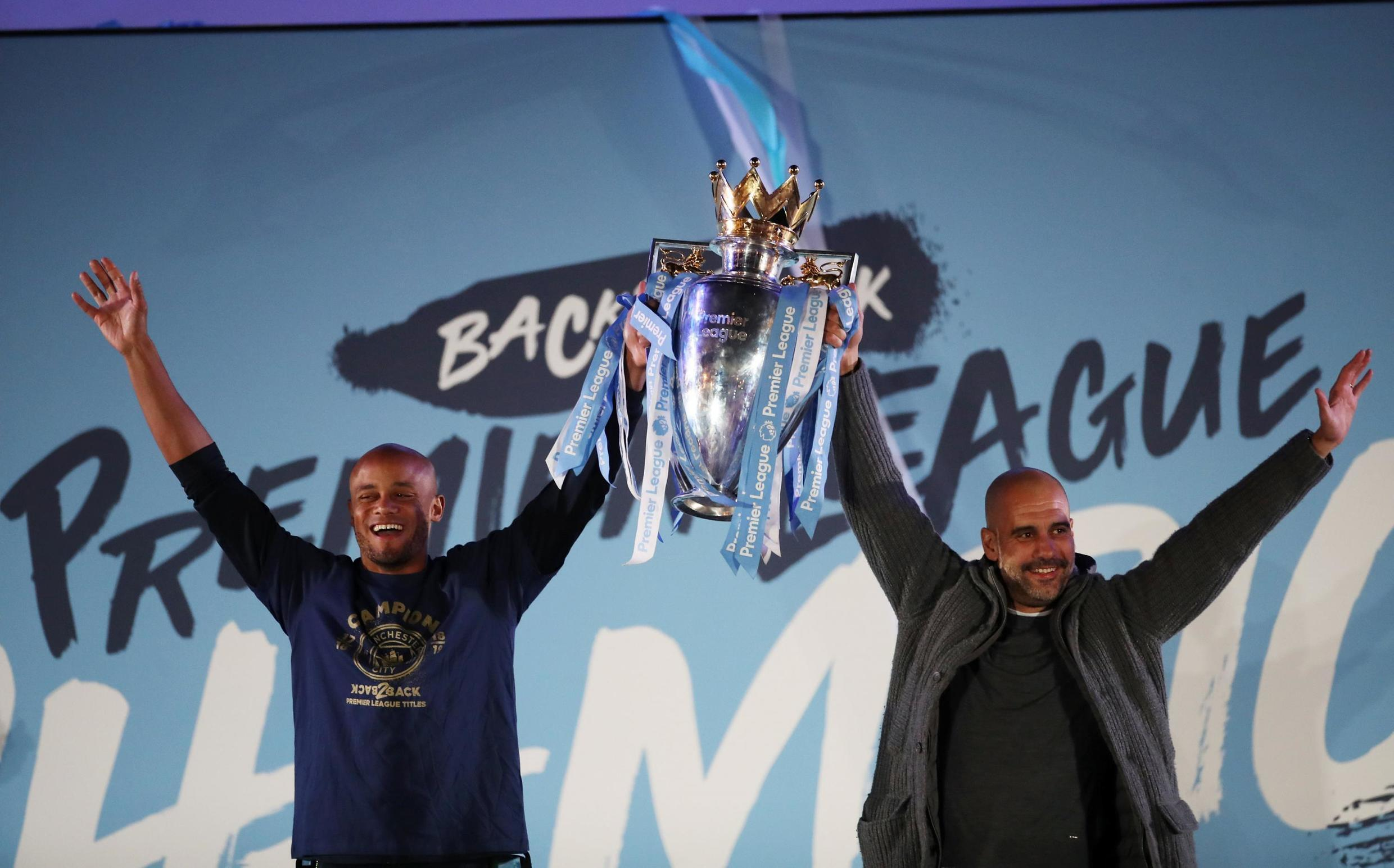 Manchester City boss Pep Guardiola (right) celebrates the retention of the English Premier League title with skipper Vincent Kompany.