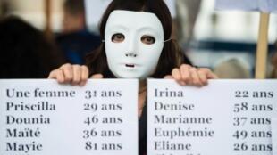 Ativista carrega cartaz com os nomes de mulheres assassinadas por seus ex-maridos e ex-companheiros na França.