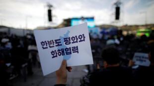 """首爾市有人舉起""""為了韓半島和平和解而協力""""的標語"""