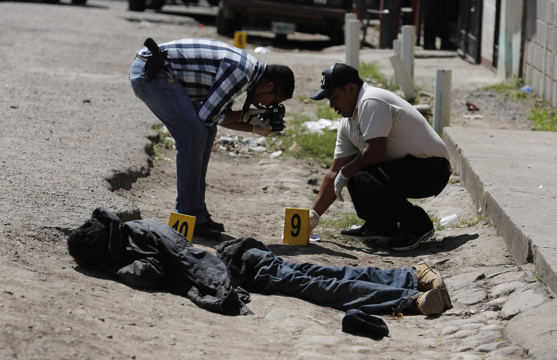 Policías examinan el cadáver de un miembro de una pandilla, en noviembre de 2013, Honduras.