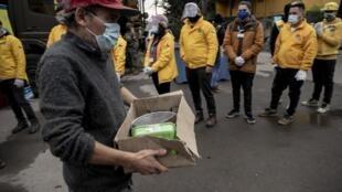 Des citoyens à revenus modestes reçoivent de la nourriture de la part de soldats chiliens, à Santiago le 16 juin 2020.