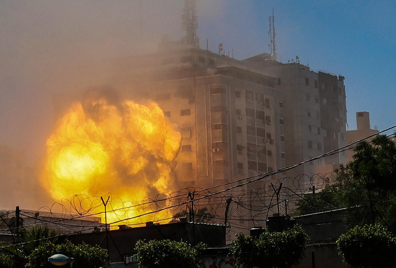 A ball of fire explodes after an Israeli air strike hits the Jala Tower in the Gaza Strip destroying the 13-storey building that house the offices of Al Jazeera television and US news agency The Associated Press