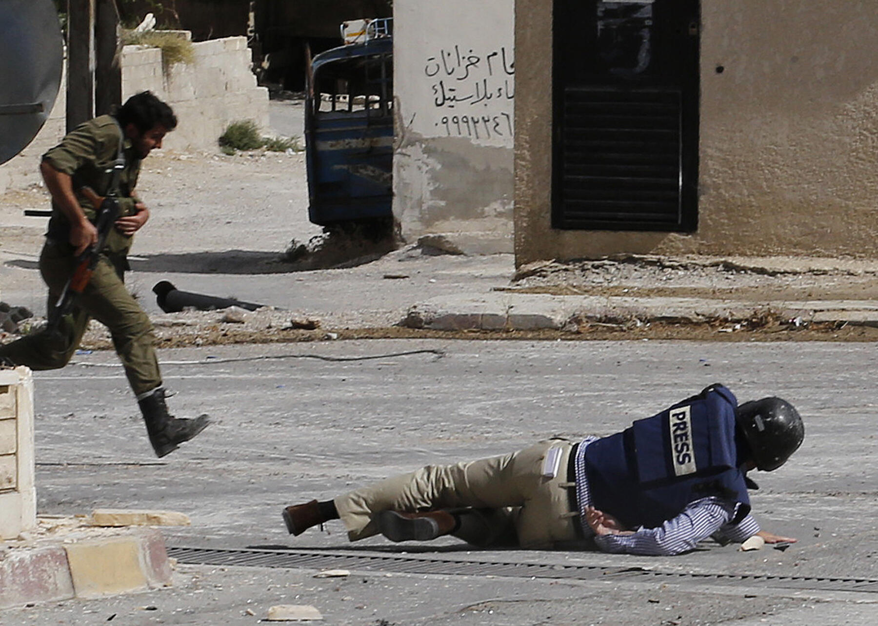 Un reporter de l'AFP Sammy Ketz rampe dans une rue de Maalula, le 18 septembre 2013 ; la Syrie a été l'un des 5 pays les plus dangereux pour les journalistes cette année.