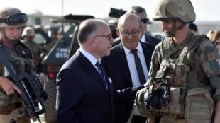 """Bernard Cazeneuve et Jean-Yves Le Drian parlent avec des soldats français de l'opération """"Barkhane"""" à Ndjamena, au Tchad, le 29 décembre 2016."""