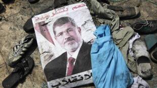 Un afiche del depuesto presidente egipcio, Mohamed Mursi, en las cercanías de la mezquita Rabaa Adawiya, en el Cairo, después de su incendio el 15 de agosto de 2013.