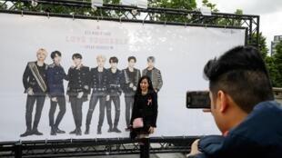 Des fans devant une affiche du groupe de K-Pop BTS avant leur concert au Stade de France, à Paris, le 7 juin 2019.