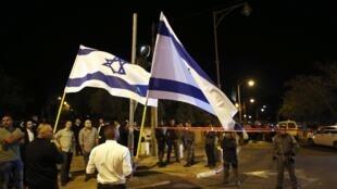 Des Israéliens agitent leur drapeau sur le lieu où un activiste d'extrême-droite a été attaqué le 29 octobre 2014, à Jérusalem.