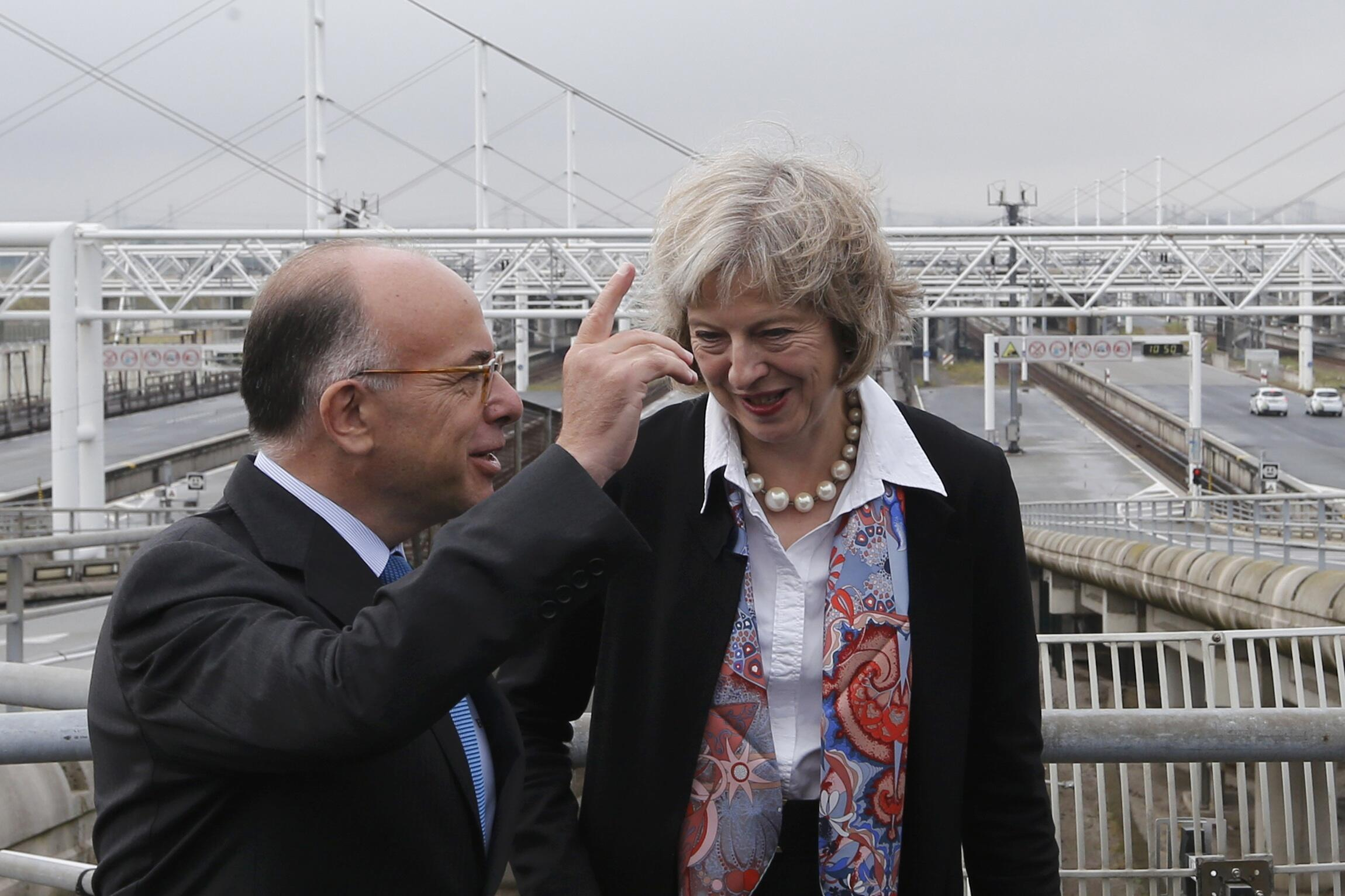French Interior Minister Bernard Cazeneuve (L) and his Britain's Theresa May  on an overpass near the Eurotunnel entrance in Calais