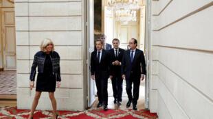 A primeira-dama Brigitte Macron avança na direção do salão de festas do Palácio do Eliseu, seguida pelo trio Sarkozy (à esquerda), Macron e Hollande (à direita).
