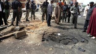 Les agents de sécurité évaluent la scène d'un attentat à la bombe du groupe islamiste Boko Haram dans la ville de Kaduna au nord du Nigeria, le 8 avril 2012