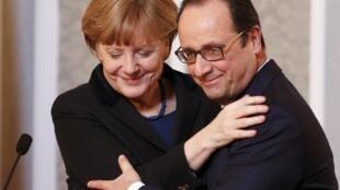 Канцлер Германии Ангела Меркель обнимает президента Франции Франсуа Олланда на встрече с журналистами после переговоров по урегулированию украинского кризиса. Минск,12 февраля 2015