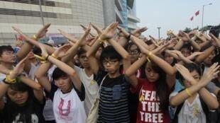 10月1日的香港國慶升旗活動場外,學民思潮召集人黃之鋒與同伴交叉雙臂以示抗議。