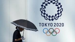 Une piétonne passe devant une affiche des JO 2020 à Tokyo.