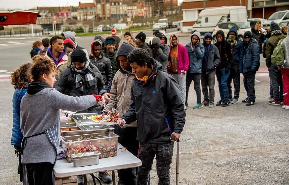 Migrantes de Calais recebem refeições de ONGs