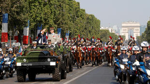 French President Emmanuel Macron and Chief of the Defence Staff French Army General Francois Lecointre arrive in a command car for the traditional Bastille Day military parade on the Champs-Elysees in Paris, France, July 14, 2018.