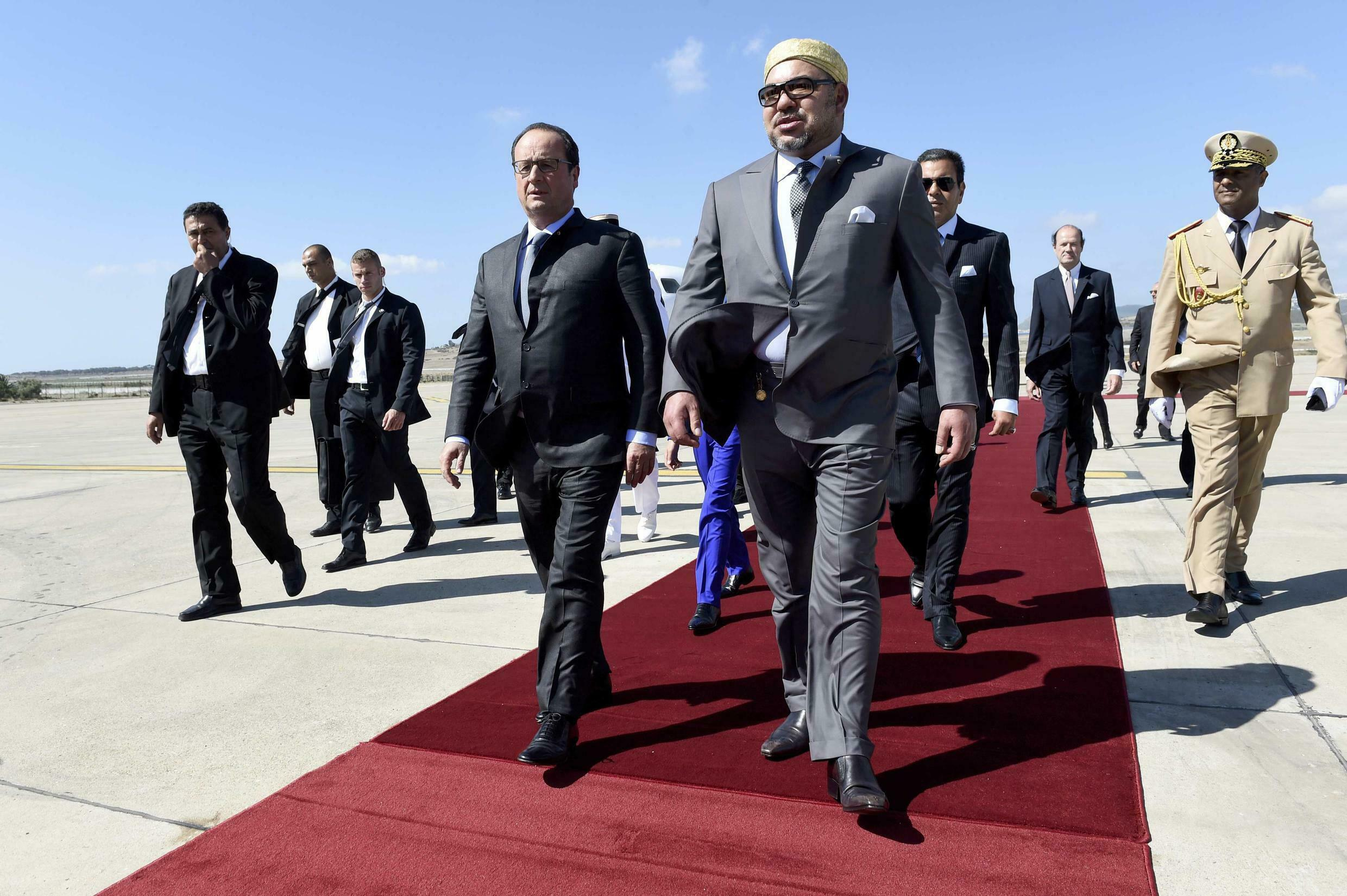 François Hollande walks with King Mohammed VI on his arrival at the airport in Tangier, 19 September 2015.