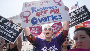 Une manifestante favorable à l'avortement encadrée de manifestants qui y sont opposés, devant les marches de la Cour suprême à Washington, aux Etats-Unis, le 27 juin 2016.