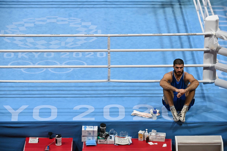 El francés Mourad Aliev permanece en el ring para protestar por su derrota ante el británico Frazer Clarke en los Juegos de Tokio-2020.