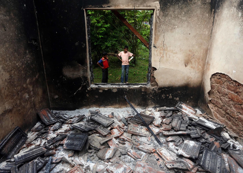 Un garçon musulman devant une maison brûlée après des heurts entre bouddhistes et musulmans, le 16 juin 2014.