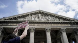 """Activista a exibir o cartaz """"Apoio aos Coletes Pretos"""". Panteão, Paris. 12 de Julho de 2019."""