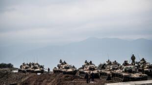 Turkish army tanks wait near the border before entering Syria