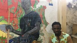 "Cameroonian artist Jean-David Nkot, with his work ""The Cleaner"" at his studio in Douala."