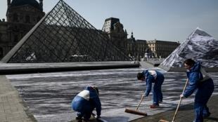 Des «colleurs» de JR sont à pied d'œuvre autour de la pyramide du Louvre.