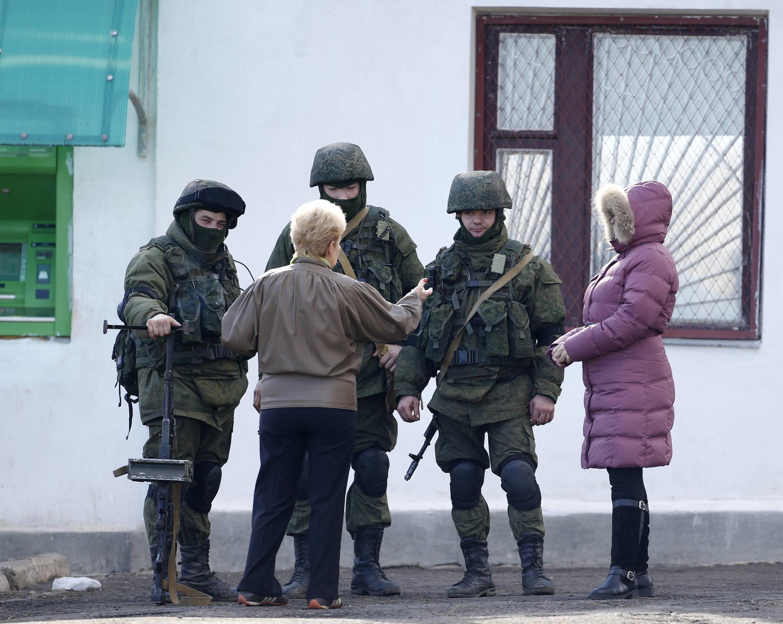 Des résidents discutent avec des hommes en armes, propablement russes, dans la banlieue de Simferopol, le 5 mars 2014.