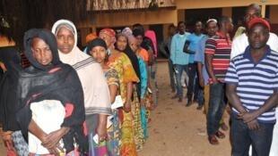 Des électeurs guinéens attendent à l'entrée d'un bureau de vote le 4 février 2018.