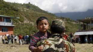 Un enfant est secouru par un soldat népalais près de Chautara, le 30 avril.