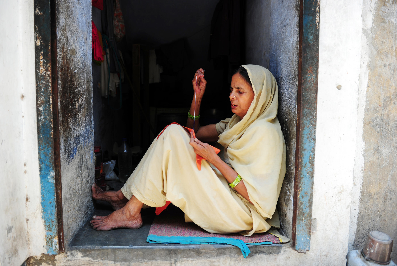 Une veuve de confession musulmane, assise à l'arrière de sa boutique à Bénarès, en Inde.