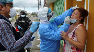 Health ministry personnel test a woman for the novel coronavirus in northern Guayaquil, Ecuador, on April 19, 2020