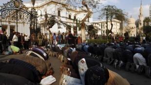 A l'heure de la prière, devant le Parlement au Caire, plusieurs dizaines de manifestants se sont alignés en direction de l'est.
