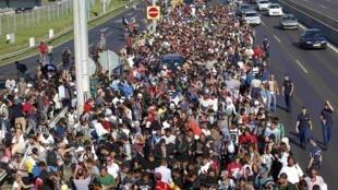 Centenas de migrantes caminham ao longo de uma rodovia de Budapeste em direção à Áustria nesta sexta-feira (4).