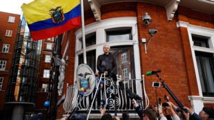 លោក Julian Assange ថ្ងៃទី១៩ ឧសភា ២០១៧ នៅមាត់បង្អួចស្ថានទូតអេក្វាទ័រ ក្នុងទីក្រុងឡុងដ៍ ជាទីដែលលោកសំងំគេចខ្លួន៥ឆ្នាំមកហើយ