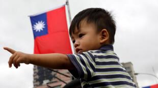 Un jeune Taiwanais captivé par le spectacle, ce lundi 10 octobre 2016 dans les rues de Taipei pour la fête nationale. Derrière, le drapeau de la République de Chine alias Taiwan, autrement dit l'ancien drapeau chinois.