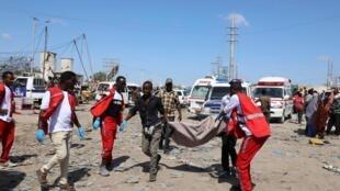 Maafisa wa idara ya uokoaji wakibeba mwili wa mtu aliyeuawa katika shambulio la bomu Mogadishu, Somalia, shambulio ambalo liligharimu maisha ya watu wengi, Jumamosi, Desemba 28, 2019.